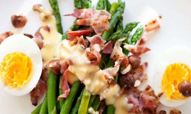 Asparagus and toasted hazelnuts served with an egg and bacon is a ...