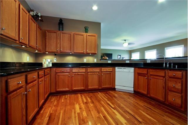 oak cabinets, multicolored floor, dark counter, brown walls  Kitchen