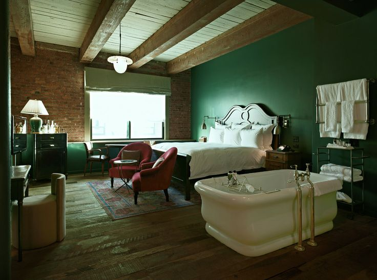 Bottle green wall, white bath and bed, traditional furniture, industrial floor and ceiling