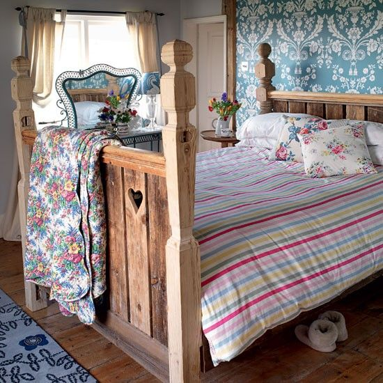 Dress a rustic bed with cottage-style prints in vibrant shades and candy-coloured stripes. The rough-hewn wood of the bed contrasts with the formal pattern of the wallpaper design set behind the bedhead.