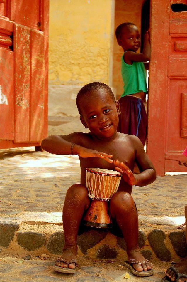 Niño jugando-practicando percusiones de su propia cultura. Africa.
