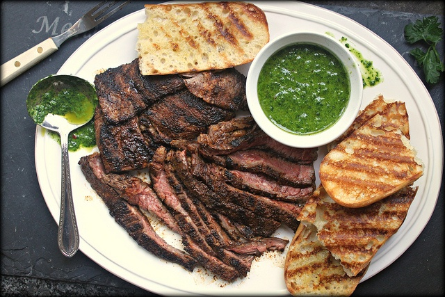 Grilled flat iron steak with chimichurri sauce and grilled bread by ...