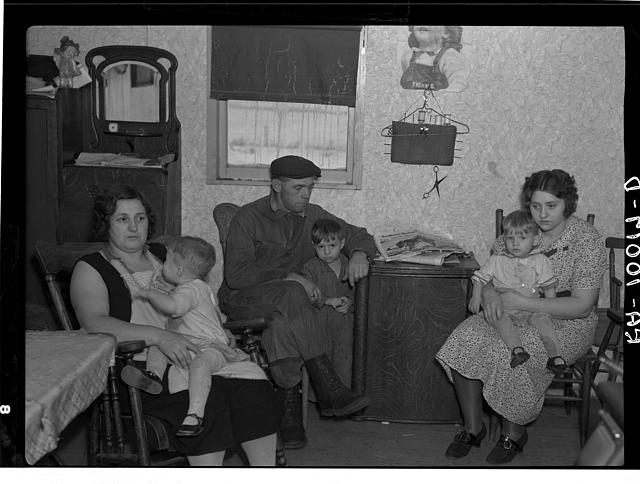 Part of the L.H. Nissen family of ten living in a three-room shack. Rest of family at school. The whole house was of unusually high humidity. The wife said they could not dry out the bedding because of the poor ventilation. This is the living room and kitchen combined. Iowa