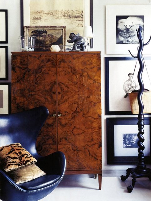 burlwood cabinet and art filled walls