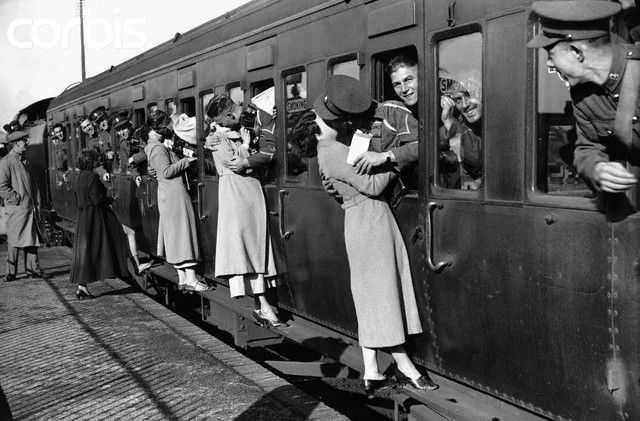 September 1935, London, England, UK --- Leaning out of train windows at Feltham Station, soldiers departing for Egypt kiss their wives and girlfriends goodbye --- Image by © Hulton-Deutsch © Corbis