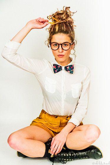 Camisa blanca cerrada al cuello con corbata de pajarita y shorts