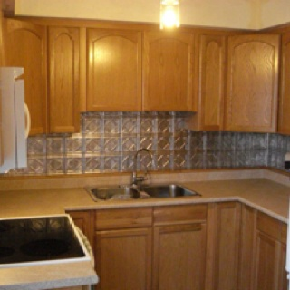 punched tin backsplash with oak stained cabinets