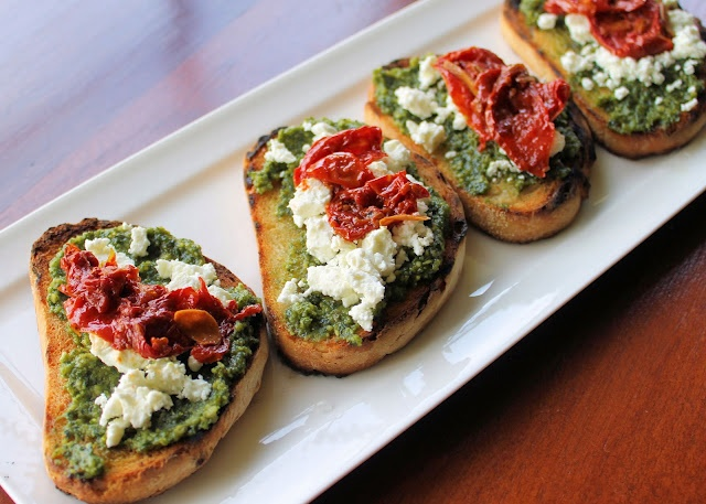 goat cheese, pesto and sun-dried tomato crostini....maybe with feta or ...