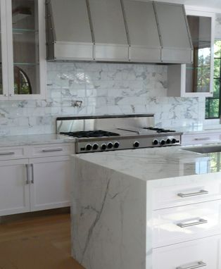 slab counter top and waterfall carrera marble tile backsplash