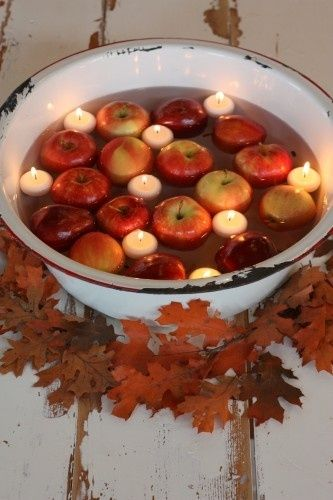 """Bobbing for apples""-styled decor. Apples & candles floating in tub. Can be used as a centerpiece or on a buffet table. Can be adapted to use at an entrance. Would use waterproof battery operated tealights."