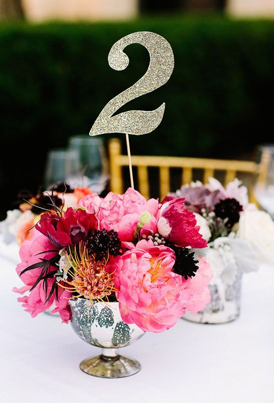 vibrant pink floral centerpiece and glitter paper table number