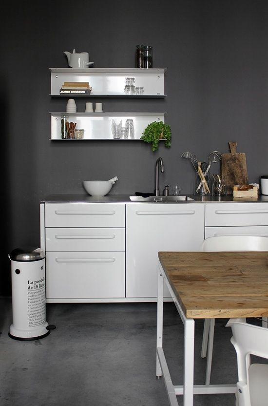 Dark gray kitchen walls behind white cabinets and shelving