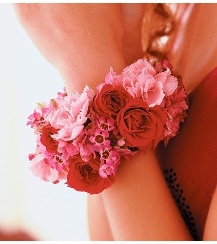 This fresh flower bracelet, made with red spray roses, ruffly pink mini-carnations, and wax flower, is a great example of a fun twist on a traditional corsage. Shop spray roses, mini-carnations, and wax flower at GrowersBox.com!
