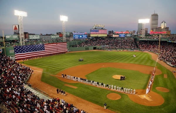"""""""A giant American flag drops down over the left field """"Green Monster"""" wall during a remembrance of 9/11 prior to the game between the Red Sox and the New York Yankees at Fenway Park in Boston."""""""