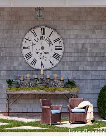 An oversize French clock face from Devonshire hangs above a Provençal table near the pool.