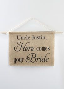 Announce the arrival of the bride with this rustic burlap sign. Personalize with the groom's name printed in black ink on burlap fabric backed with natural colored canvas. Raw edges complete the rustic look. #rusticweddings #davidsbridal