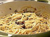 Spaghetti alla Carbonara    1 pound spaghetti  2 cups cubed pancetta rind removed  2 teaspoons olive oil  1/4 cup dry white wine or vermouth  4 eggs  1/2 cup freshly grated Parmesan  1/4 cup heavy cream  Freshly ground black pepper  Freshly ground nutmeg