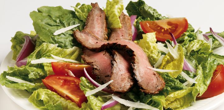 ... flank steak served over a bed of Romaine lettuce, cherry tomatoes, red
