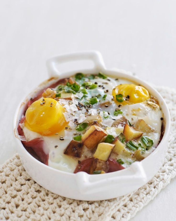 Eggs are baked with potatoes, ham and green onions in individual ...