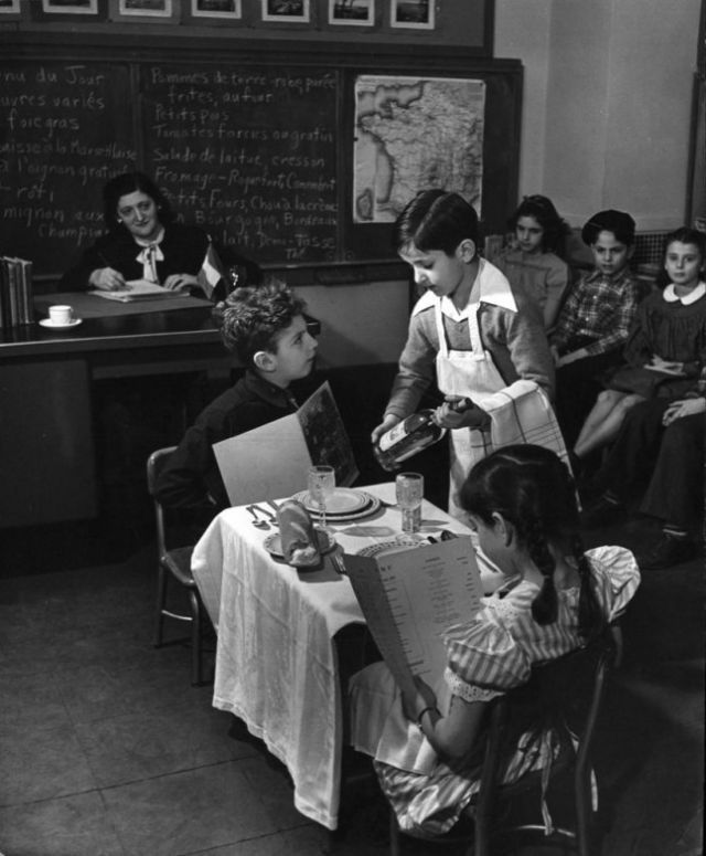 U.S. Practical conversation in French by 9-year-olds. Here waiter asks gentleman to approve the wine, as lady consults French menu. New York's Hunter College, 1948 // By Nina Leen