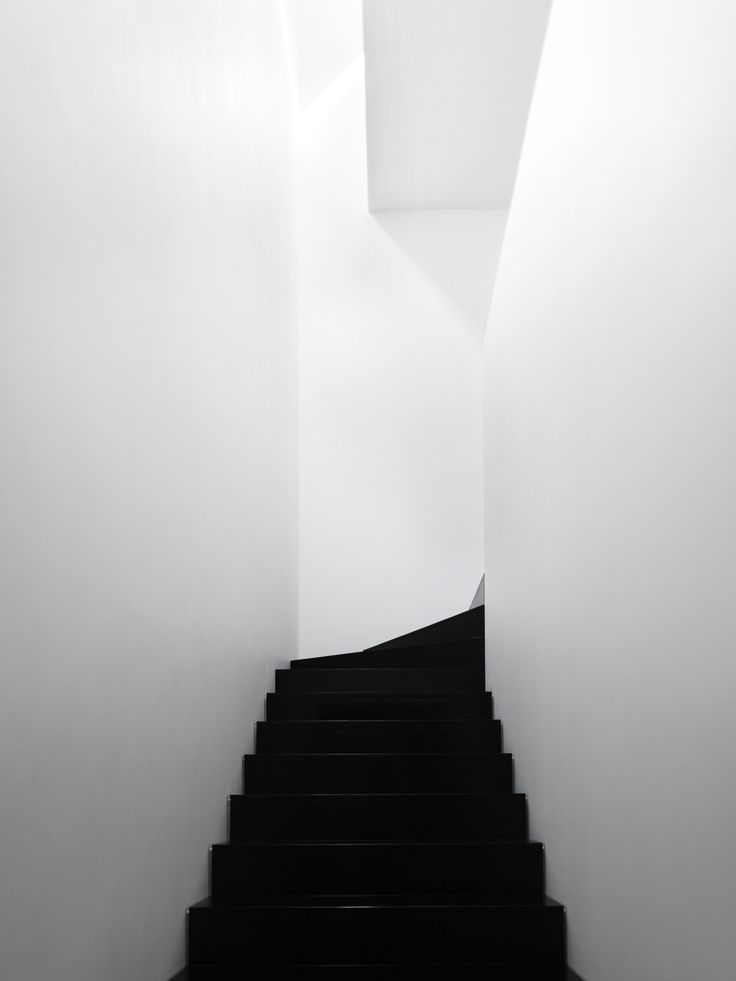 Black minimalist staircase white walls skylight