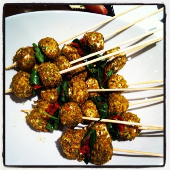 Goat cheese balls wrapped in crushed pistachios, skewered with basil ...