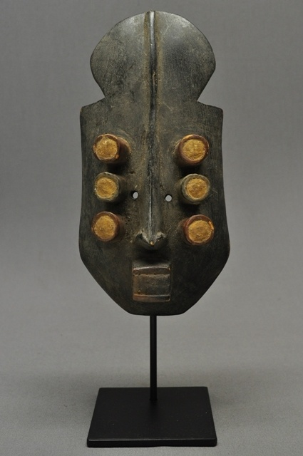 """Grebo Mask - Liberia - This is a small carved wood Grebo mask with black, white and red pigment. It has 6 tubular eyes and has been mounted on a custom iron stand for display. The mask is 10"""" long and the overall height on stand is 13 1/4""""."""