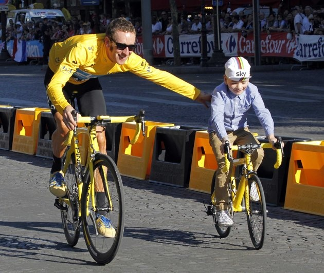 Sky Procycling rider and leader's yellow jersey Bradley Wiggins of Britain rides with his son Ben on the Champs Elysees after winning the 99th Tour de France cycling race in Paris, July 22, 2012