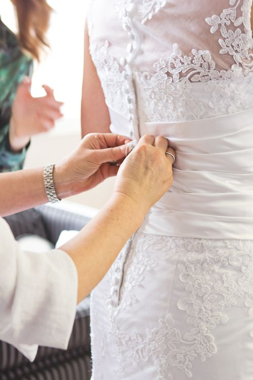 A colour image of a bride's wedding dress being done up