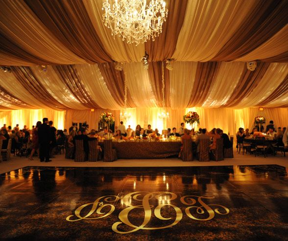 Brown and cream fabric is draped across the ceiling to create an elegant tented look, complete with a chandelier and a gold monogram on the dance floor.