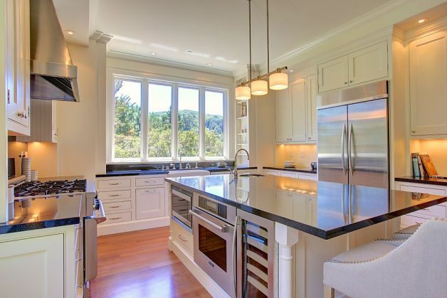 The kitchen features white cabinets with exposed hinges, and a center