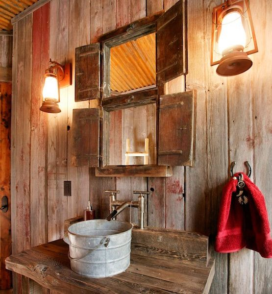 tiny bathrooms that are big on style....Into the Woods    This take on rustic style is fun with in-theme lanterns, a metal bucket sink and reclaimed wood boards on the walls.