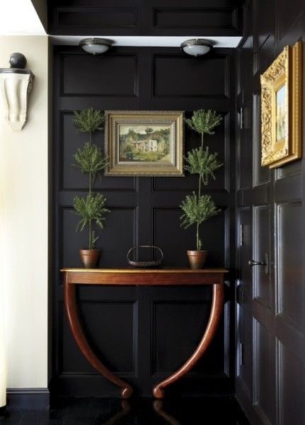board and batten wall panels in black, a wood table, topiaries, and gilt framed prints make a lasting impression