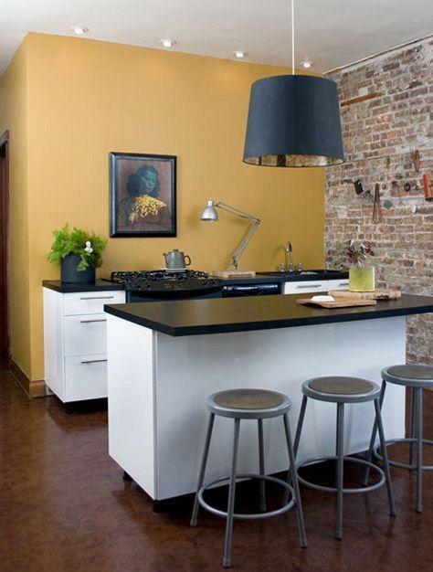 Mustard yellow paint + white cabinets + brick accent wall + hardwood