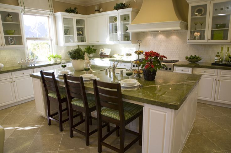 White and green kitchen with matching island with seating for three