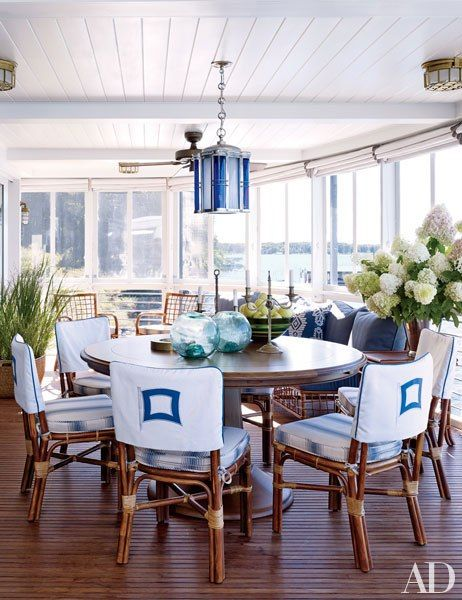In the sunroom, a bespoke table by Blatt Billiards is grouped with a suite of Bielecky Brothers chairs; the hanging lantern is by Jamb, and the seat cushions are covered in a Rose Tarlow Melrose House fabric