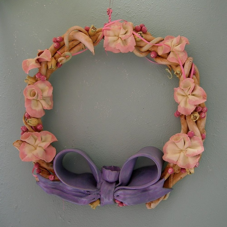 """Porcelain Flower Wreath with a Purple Bow"" by Cecily Smith Maples This hand-built porcelain wreath fired to cone 9-10 in oxidation was made during the early 1990's. I was working out of a barn at the time."