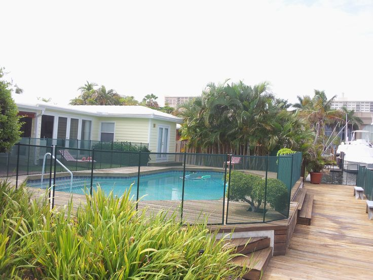 Green pool fence installed on wooden deck in fort for Pool design fort lauderdale