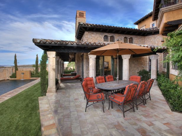 Orange patio chairs add a shot of color to this neutral Italian-style backyard.