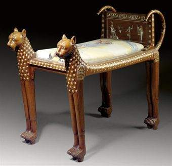 AN EGYPTIAN REVIVAL MOTHER OF PEARL-INLAID SOLID ROSEWOOD STOOL**  CIRCA 1900  Formed as two dogs flanking a slip seat and an inlaid back panel of ancient Egyptian scenes  26 in. (66 cm.) high, 15½ in. (38.5 cm.) wide, 35 in. (89 cm.) deep