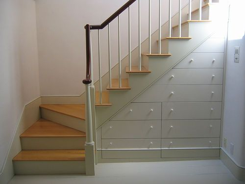 Storage beneath a curved stair.