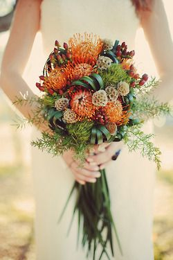 Fun!  Orange pin cusion proteas, scabiosa pods, lily grass folds, foxtail ferns, burgundy hypericum berries and green trix.