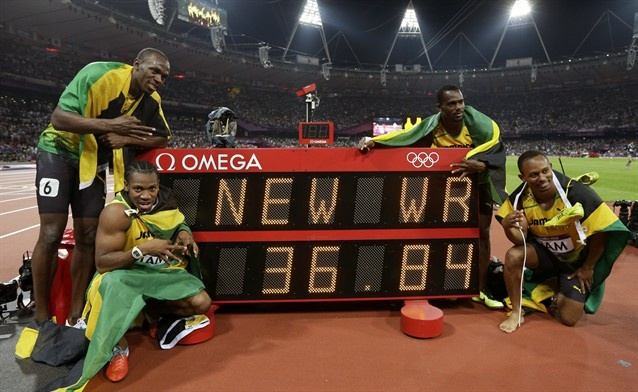 Jamaica's Usain Bolt, Yohan Blake, Nesta Carter and Michael Frater next to a timing board displaying their world record time of 36.84.
