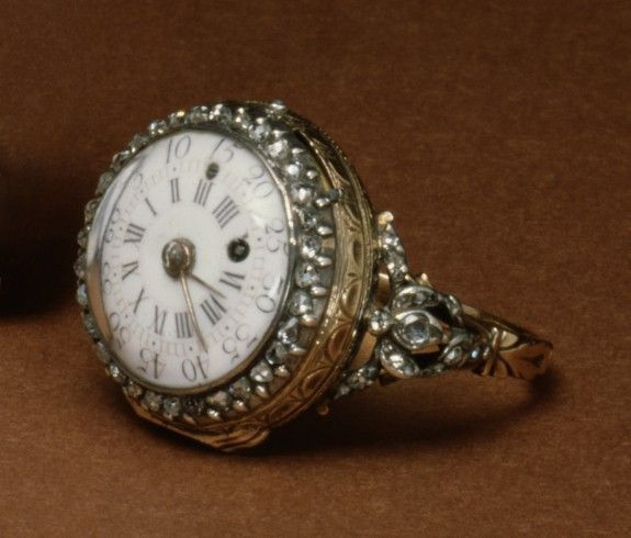 Ring watch, French, c1780. The white dial is surrounded by a ring of brilliants. The stones are mounted to form floral sprays on the pierced shoulders of the ring.