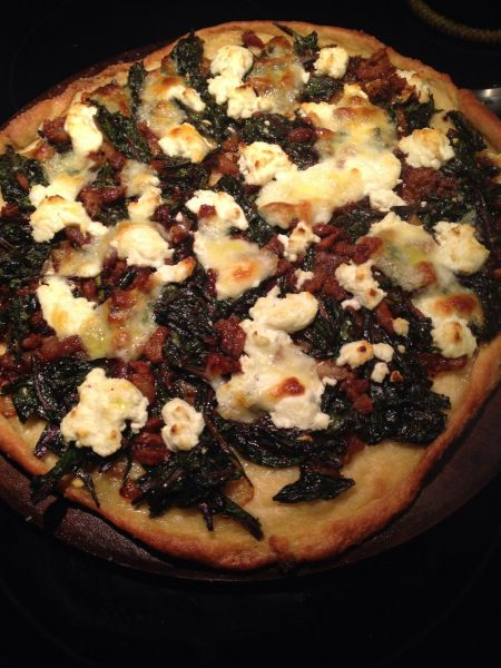 Pizza topped with dandelion greens, goat cheese, caramelized onions ...