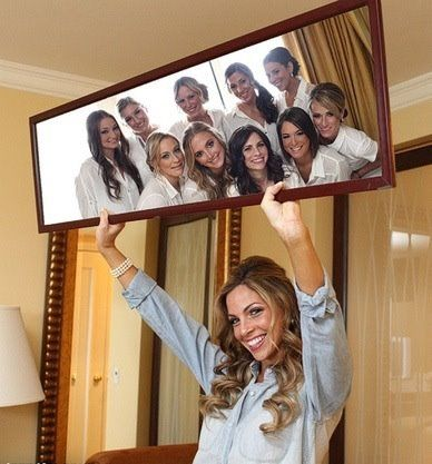 Bride holding a mirror and her Bridesmaids in the mirror! This is too cute