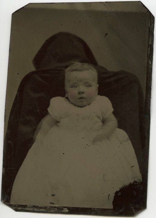 This was a practice where the mother, often disguised or hiding, often under a spread, holds her baby tightly for thephotographer to insure a sharply focused image