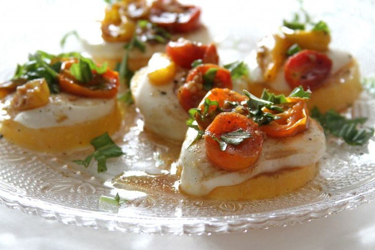 ... polenta is topped with creamy mozzarella, roasted tomatoes, and fresh