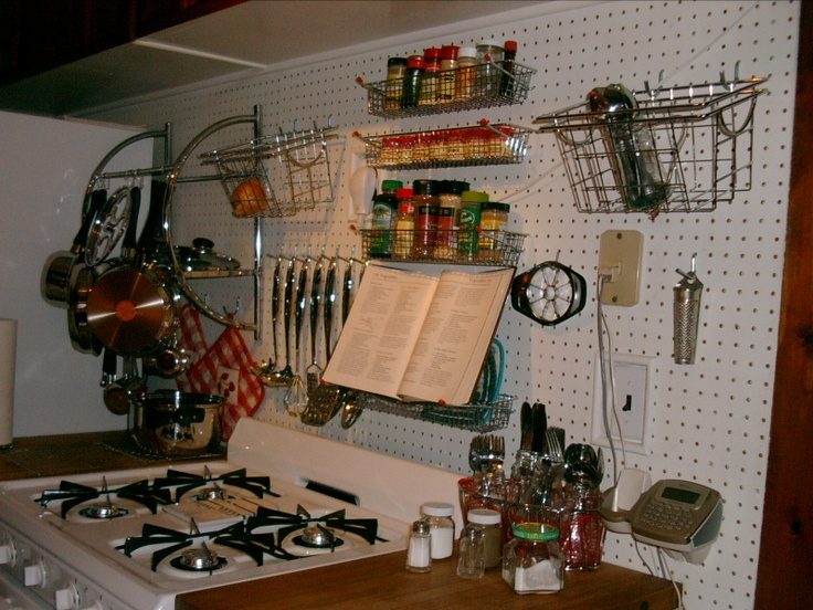 Pegboard in the kitchen of a rental fitted out with chrome shelving, hooks & hangers.