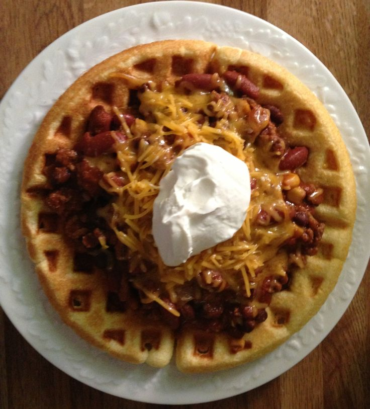 Chili over cornbread waffles topped with cheddar cheese and sour cream